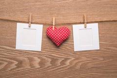 Dos fotos inmediatas en blanco con los corazones en fondo de madera Imágenes de archivo libres de regalías