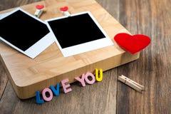 Dos fotos inmediatas en blanco con los corazones rojos En fondo de madera Imagen de archivo libre de regalías
