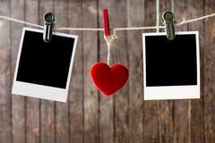 Dos fotos inmediatas en blanco que cuelgan en la cuerda para tender la ropa Imagen de archivo libre de regalías