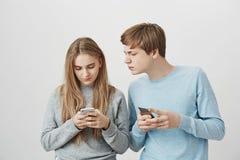 Dos frikis del smartphone que fijan las nuevas fotos en red social Retrato de amigos lindos enfocados con el pelo justo, sostenié imágenes de archivo libres de regalías