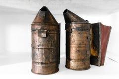 Dos fumadores oxidados, polvorientos y muy viejos de la abeja colocados en el estante blanco Fotos de archivo libres de regalías