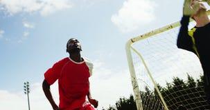 Dos futbolistas que saltan para pegar una bola almacen de video