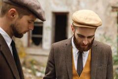 Dos gángsteres con una barba se colocan en la calle y eso que están mirando de mirada abajo retro outdoors Imagenes de archivo