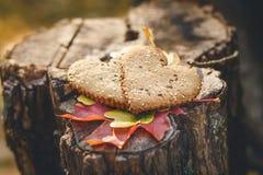 Dos galletas de la forma del corazón están en el Stumb de madera con las hojas otoñales Fondo de la naturaleza Foco selectivo ent Imagen de archivo libre de regalías