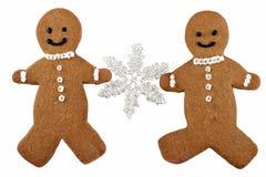 Dos galletas del hombre de pan de jengibre que sostienen un copo de nieve Imagenes de archivo