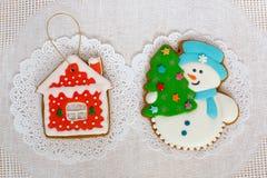 Dos galletas del pan de jengibre en la forma del árbol de navidad, del muñeco de nieve y de la pequeña casa en un fondo blanco de Fotografía de archivo libre de regalías