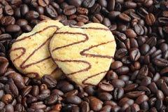 Dos galletas en forma de corazón en los granos de café Imagen de archivo