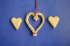 Dos galletas en la forma de corazones en un fondo y un corazón azules de la ejecución hechos de la paja Fondo del concepto del am Foto de archivo libre de regalías