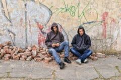 Dos gamberros de la calle que se oponen a una pared pintada pintada se están preparando para fumar un cigarrillo Imágenes de archivo libres de regalías