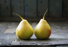 Dos gemelos amarillos de la pera en el piso de madera, aún vida Foto de archivo