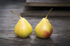 Dos gemelos amarillos de la pera en el piso de madera, aún vida Imágenes de archivo libres de regalías