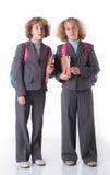 Dos gemelos con el libro de textos Imagenes de archivo