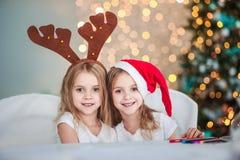 Dos gemelos de las hermanas en los trajes Santa Claus y los cuernos de los ciervos en el interior adornado contra el contexto de  Imágenes de archivo libres de regalías