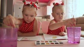 Dos gemelos de las pequeñas hermanas son felices de pintar dibujos con las acuarelas que se sientan en la tabla juntos almacen de metraje de vídeo