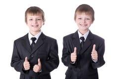 Dos gemelos de los niños pequeños en los pulgares de los trajes de negocios para arriba aislados en wh Imagen de archivo libre de regalías