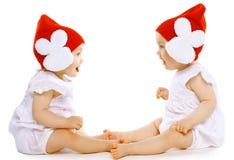 Dos gemelos divertidos del bebé en sombreros Imágenes de archivo libres de regalías