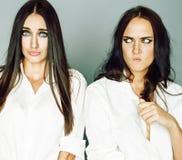 Dos gemelos presentaci?n de las hermanas, haciendo el selfie de la foto, vistieron la camisa blanca, amigos diversos del peinado, fotografía de archivo