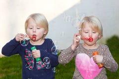 Dos gemelos rubios hermosos que soplan burbujas Imagenes de archivo