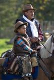 Dos generaciones de vaqueros en silla de montar Fotografía de archivo libre de regalías