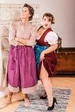 Dos generaciones divertidas de dos mujeres en dirndl Imagenes de archivo