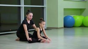 Dos gimnastas artísticos de las hermanas lindas delgadas de las muchachas en ropa de deportes negra hacer calentamiento en gimnas