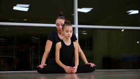 Dos gimnastas art?sticos de las hermanas lindas delgadas de las muchachas en ropa de deportes negra hacer calentamiento en gimnas