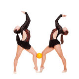 Dos gimnastas sonrientes que presentan con la bola amarilla Foto de archivo