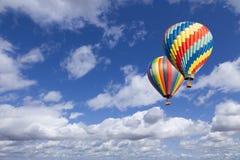 Dos globos del aire caliente en el cielo azul hermoso Imágenes de archivo libres de regalías