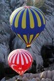 Dos globos del aire caliente flotan abajo de un valle cerca de Goreme en la región de Cappadocia de Turquía Foto de archivo libre de regalías