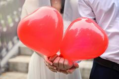 Dos globos rojos bajo la forma de corazones en las manos de los recienes casados Imágenes de archivo libres de regalías