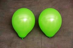 Dos globos verdes contra el papel pintado marrón Imagen de archivo
