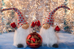 Dos gnomos alegres con las manos que detienen vagos de cristal rojos de la Navidad Foto de archivo libre de regalías