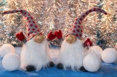 Dos gnomos alegres con las manos suben y snowbal blanco decorativo Foto de archivo libre de regalías