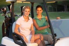 Dos golfistas femeninos que montan en cochecillo del golf Imágenes de archivo libres de regalías