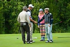 Dos golfistas sacuden las manos en feeld del golf Fotografía de archivo libre de regalías