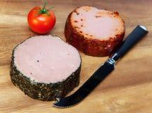 Dos gomas de la carne, cuchillo especial y tomate. Aún-vida en un día soleado Imagen de archivo libre de regalías