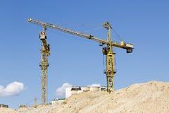 Dos grúa amarillos de la construcción contra el cielo azul Imágenes de archivo libres de regalías