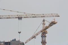 Dos grúa en la construcción de un edificio alto fotos de archivo
