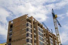 Dos grúa que trabajan en el alto edificio de ladrillo de la subida bajo construcción en copia soleada azul del cielo espacian el  imagen de archivo libre de regalías