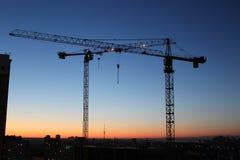 Dos grúas de construcción con el cielo de la puesta del sol de la pendiente fotografía de archivo libre de regalías