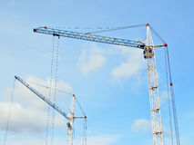 Dos grúas de construcción en un fondo del cielo azul Imágenes de archivo libres de regalías