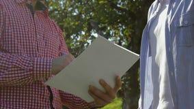 Dos granjeros irreconocibles concluyen un acuerdo en el manzanar almacen de metraje de vídeo
