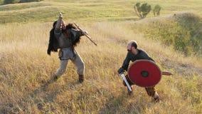 Dos guerreros medievales Viking están luchando con las espadas y los escudos almacen de metraje de vídeo