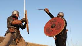Dos guerreros Viking están luchando con las espadas, con las tapas, los escudos en el prado metrajes