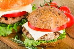 Dos hamburguesas en el tablero de madera Imagen de archivo