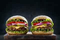 Dos hamburguesas en un tablón de madera rústico fotografía de archivo libre de regalías