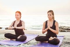 Dos hembras caucásicas jovenes que practican yoga en la playa imágenes de archivo libres de regalías