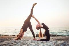Dos hembras caucásicas jovenes que practican yoga en la playa foto de archivo