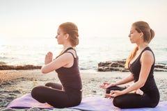 Dos hembras caucásicas jovenes que practican yoga en la playa imagenes de archivo
