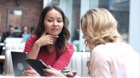 Dos hembras hermosas en café usando la tableta de Digitaces foto de archivo